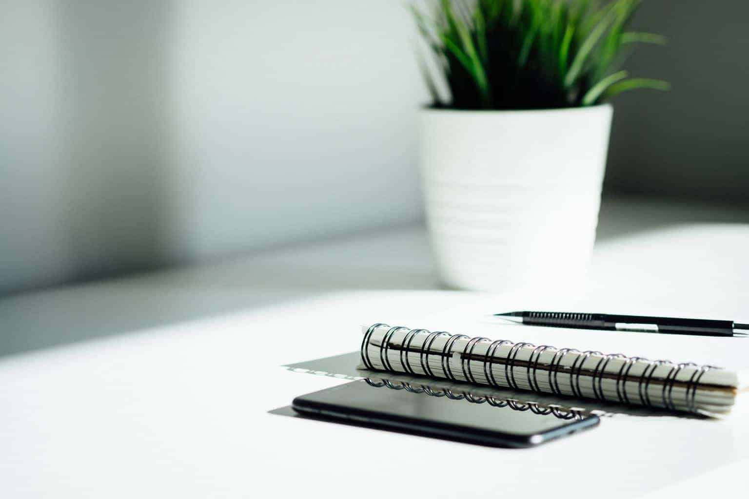 pen, notebook, and smartphone on a white table with plant