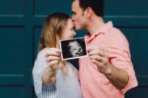 Man and woman holding an ultrasound picture of their sweet baby