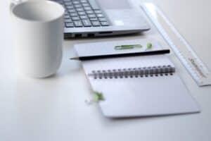 black pencil on ruled notepad beside white ceramic mug and grey laptop
