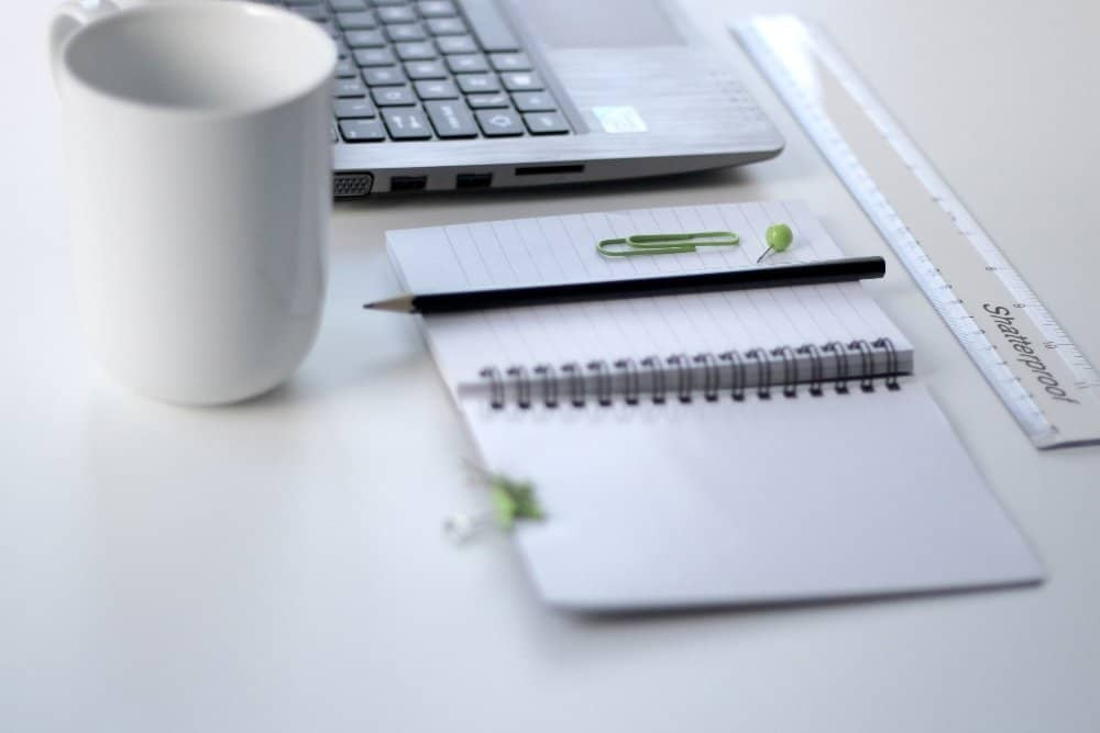 black pencil on ruled notepad beside white ceramic mug and grey laptop