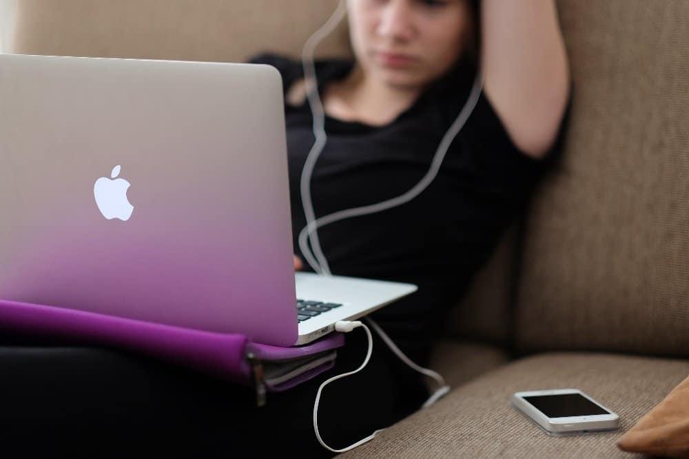 teen sitting on sofa with MacBook