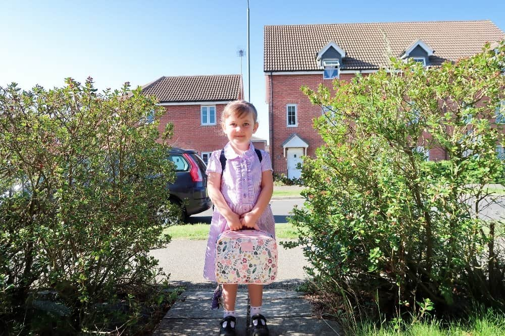 child standing in school uniform next to green shrubbery