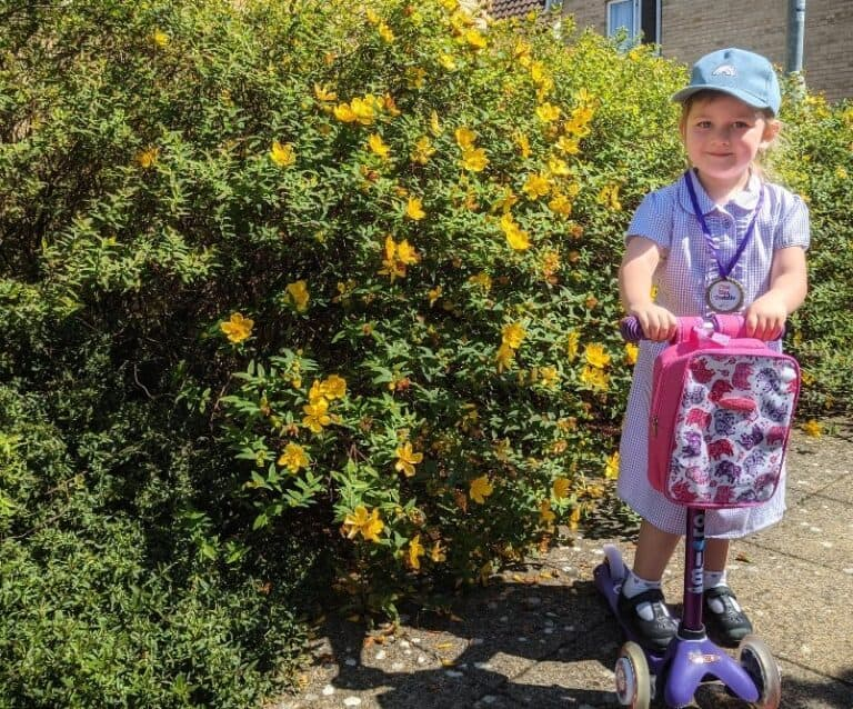 child in school uniform on a purple scooter
