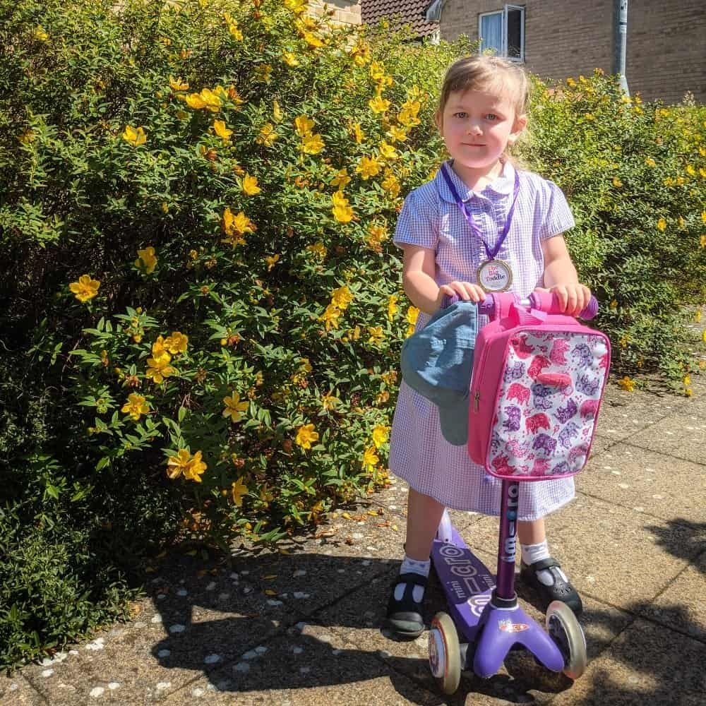 child in school uniform standing with purple microscooter