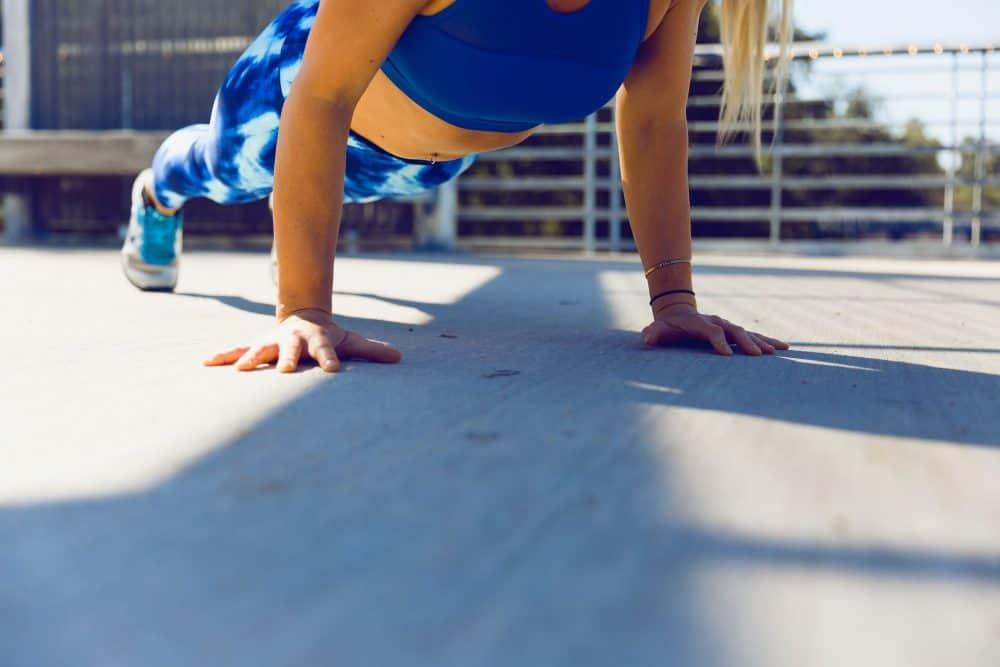 woman planking on grey asphalt