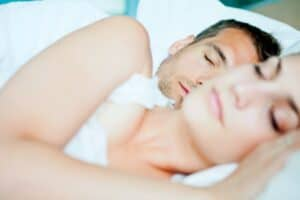 Sleeping together on white bedsheets