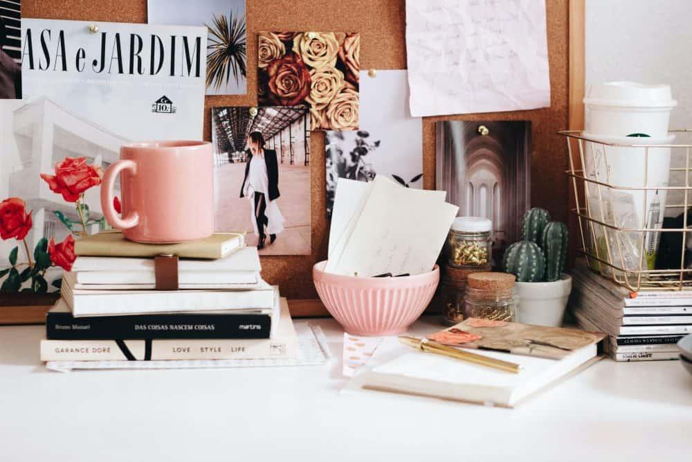 pink mug on stacked books on a desk