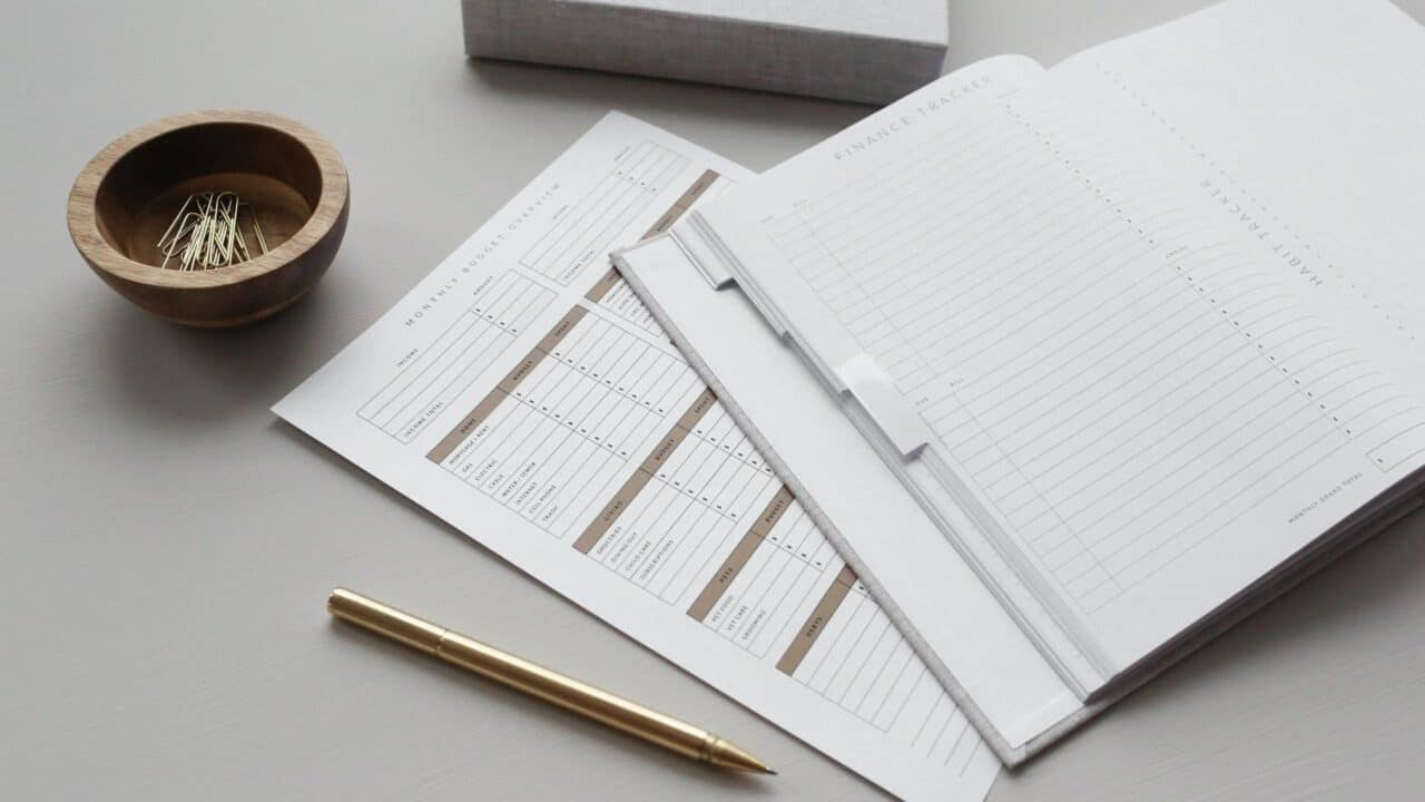 white finance tracker spreadsheet and stationery