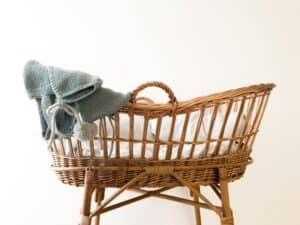 grey textile hanging on a wicker baby basket