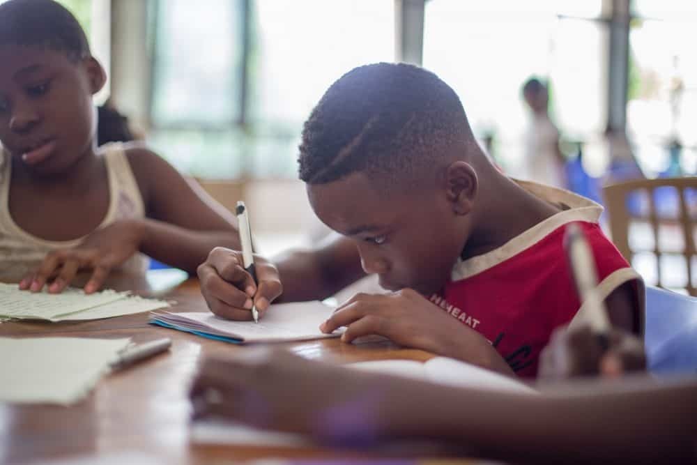 boy writing on paper at desk