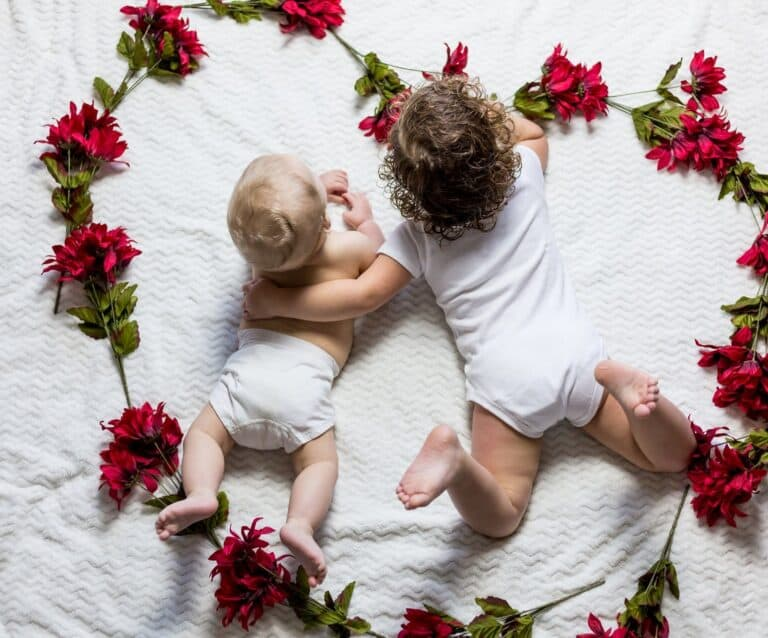 two baby's lying on a white sheet surrounded by flowers