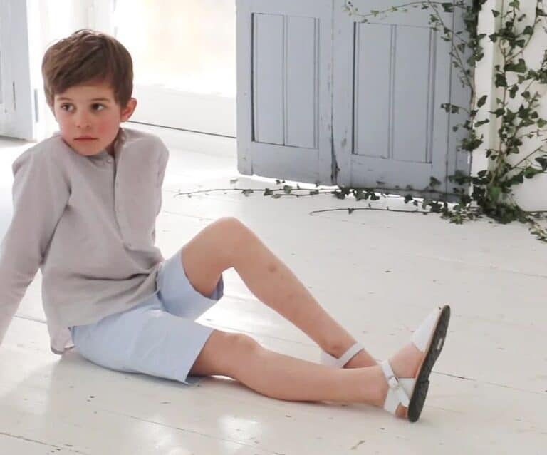 child sitting on a white wooden floor in shorts and a shirt