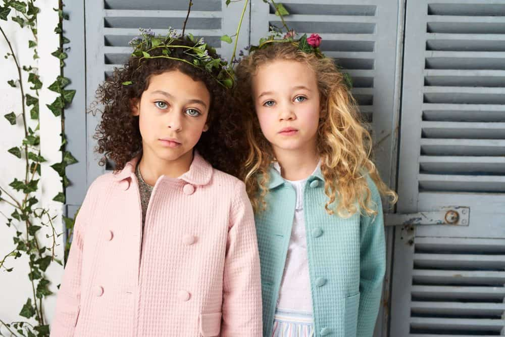 two children standing against shutters wearing coats