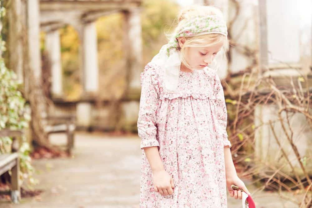 child standing in gardens with floral dress