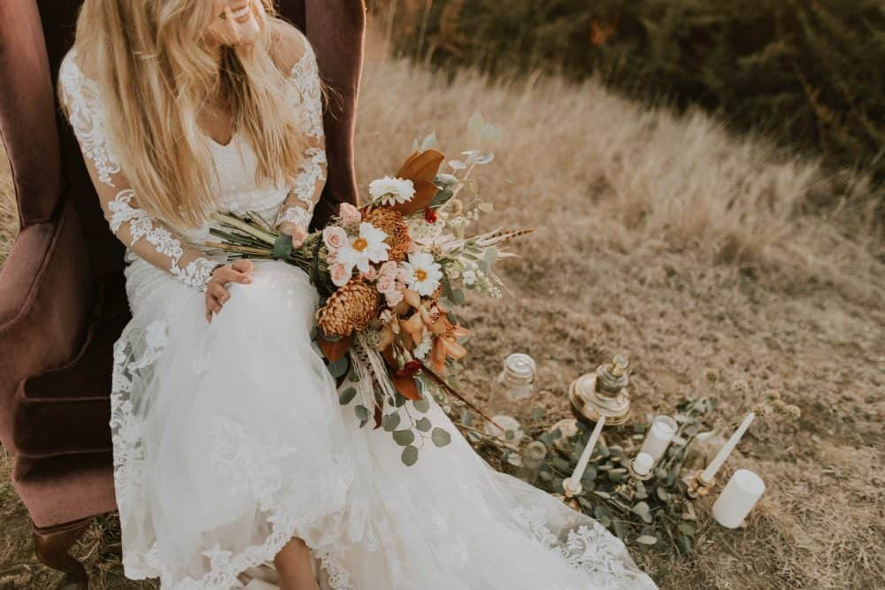 woman in white bridal gown sitting on brown winged chair with bouquet