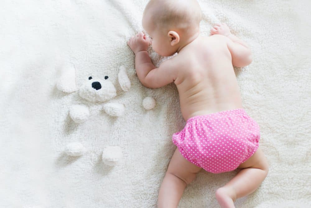 baby crawling with a pink cloth nappy
