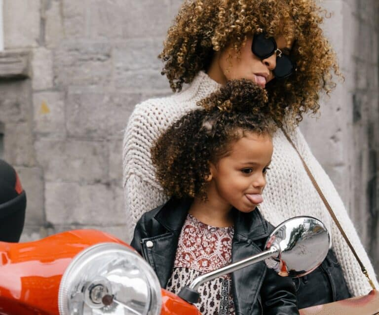 woman and girl showing their tongues besides a motorcycle mirror