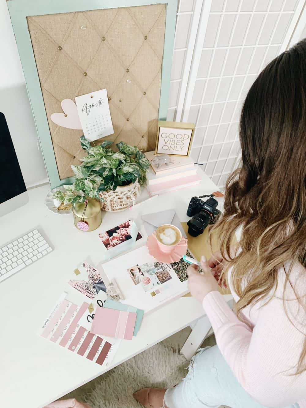 Branding process on a pink desk with candles, coffee, pantone colors and plants