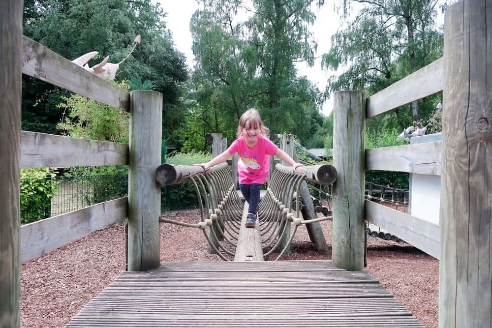 child in a pink Frugi top playing on a wooden climbing frame