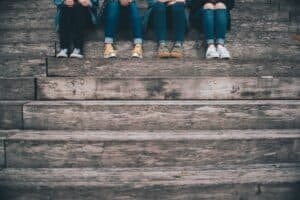 life skills for teens - four teenagers sitting on wooden steps
