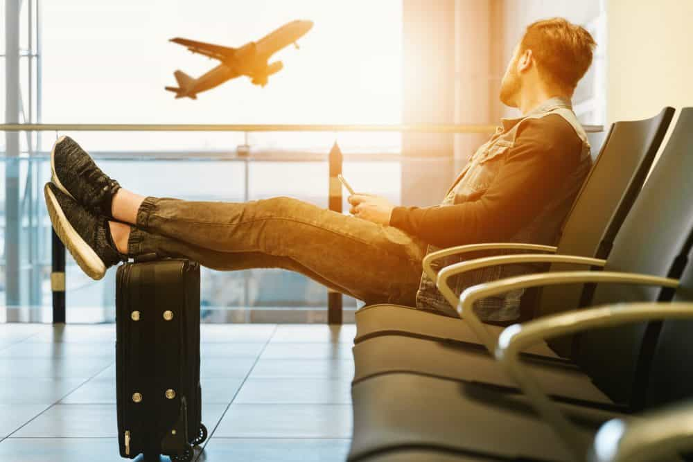 man sitting in an airport lounge with suitcase
