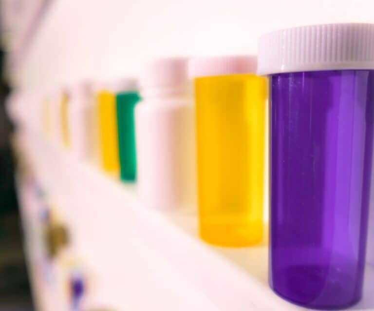 shelves of pill bottles with thousands of pills on the floor