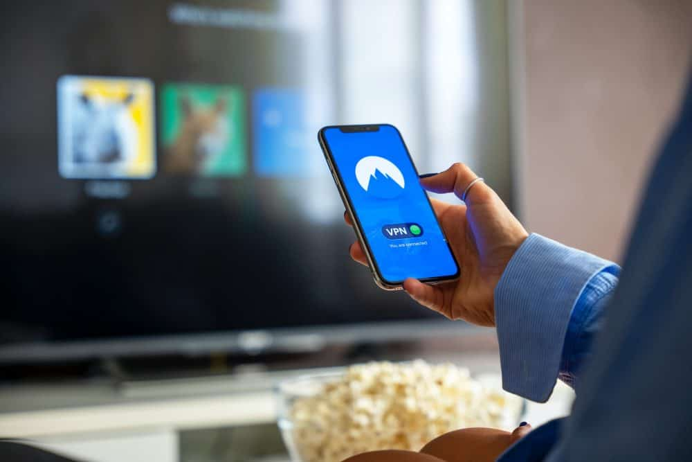 Mobile phone in front of a TV screen with popcorn